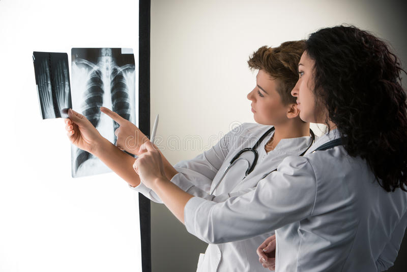 Due giovani medici attraenti che esaminano raggi x immagine stock libera da diritti