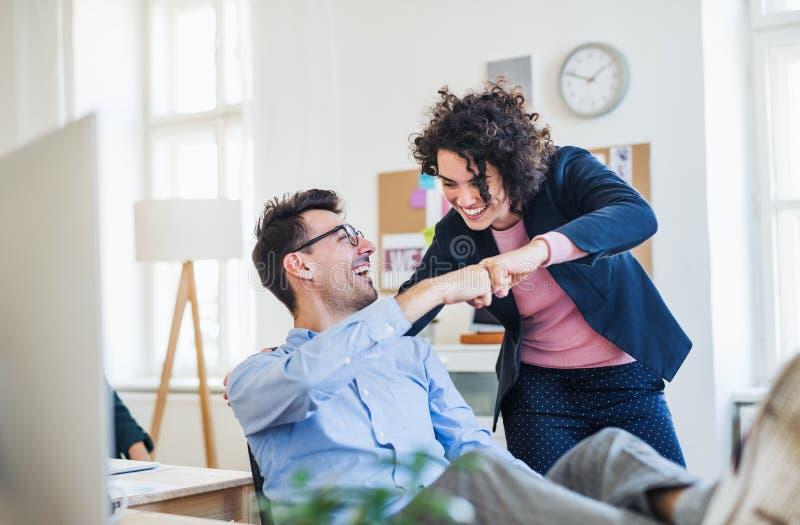 Due giovani persone di affari allegre in un ufficio moderno, facente l'urto del pugno fotografia stock libera da diritti