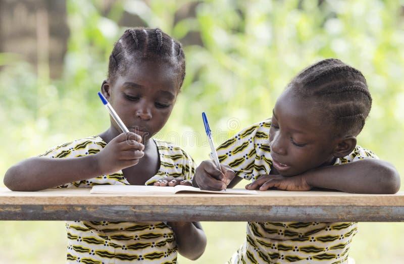 Due giovani ragazze africane che scrivono all'aperto immagini stock