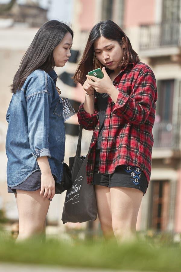 Due giovani ragazze cinesi turistiche che esaminano il telefono cellulare sulla via a Barcellona della Spagna immagini stock