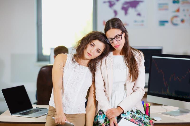 Due giovani ragazze di affari in bluse bianche all'ufficio sono stanche fotografia stock libera da diritti