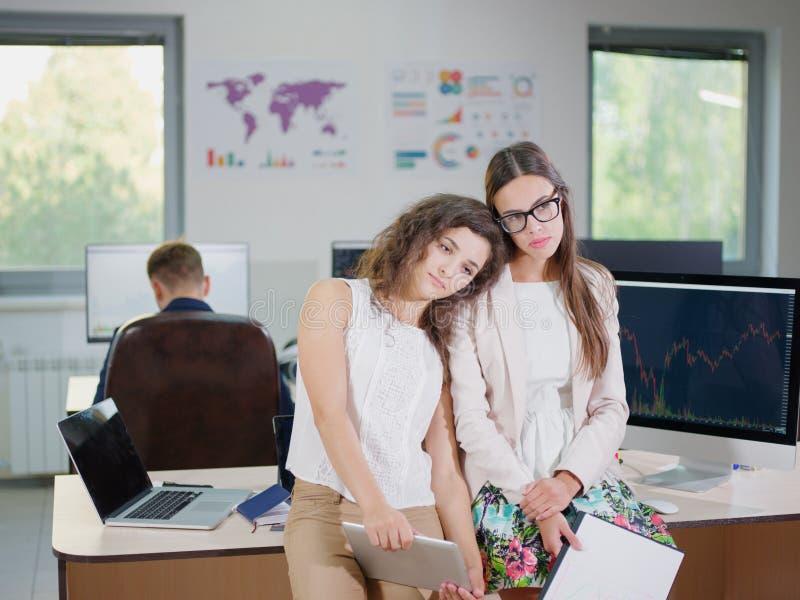 Due giovani ragazze di affari in bluse bianche all'ufficio sono stanche immagine stock