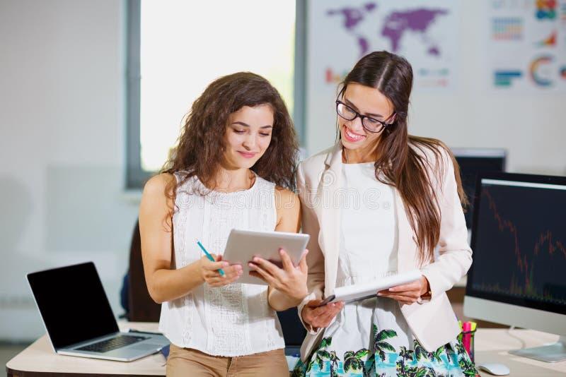 Due giovani ragazze di affari stanno esaminando i documenti e una compressa fotografia stock