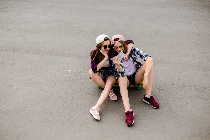 Due giovani ragazze felici in attrezzatura dei pantaloni a vita bassa che si siede insieme sul longboard e che fa selfie sul tele fotografie stock libere da diritti