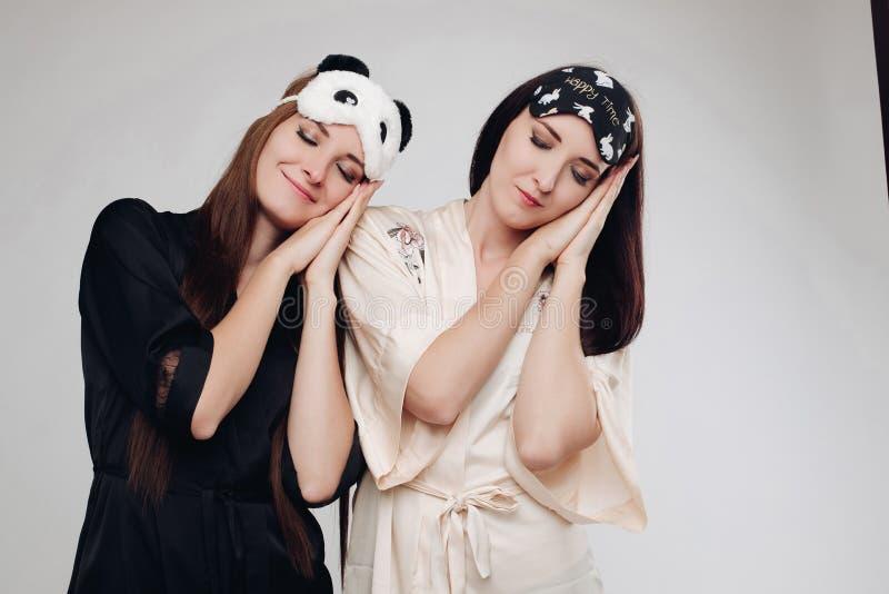 Due giovani ragazze stanche che indossano sonno dei pigiami immagine stock