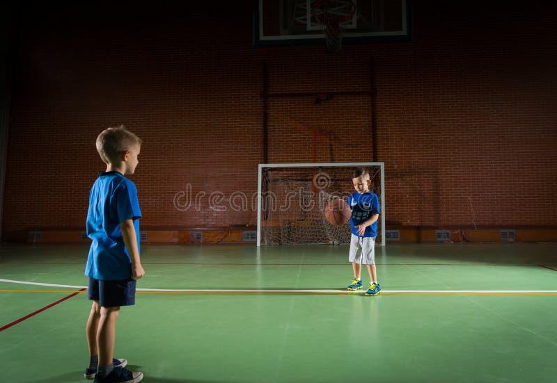 Due giovani ragazzi che giocano con una pallacanestro fotografie stock