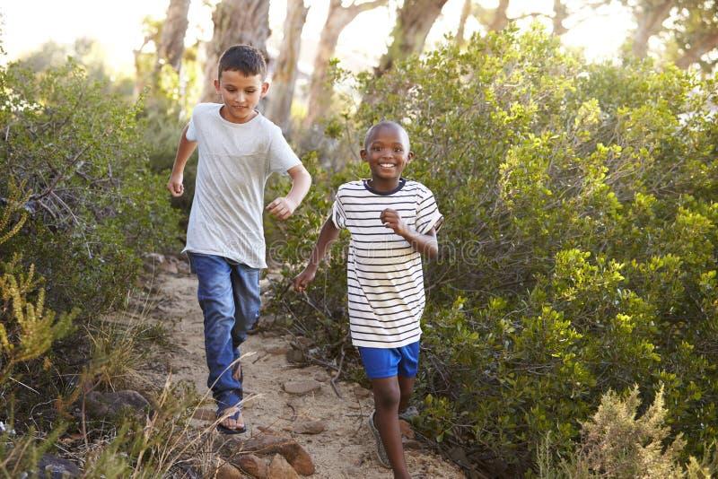 Due giovani ragazzi sorridenti che corrono su un sentiero nel bosco immagine stock