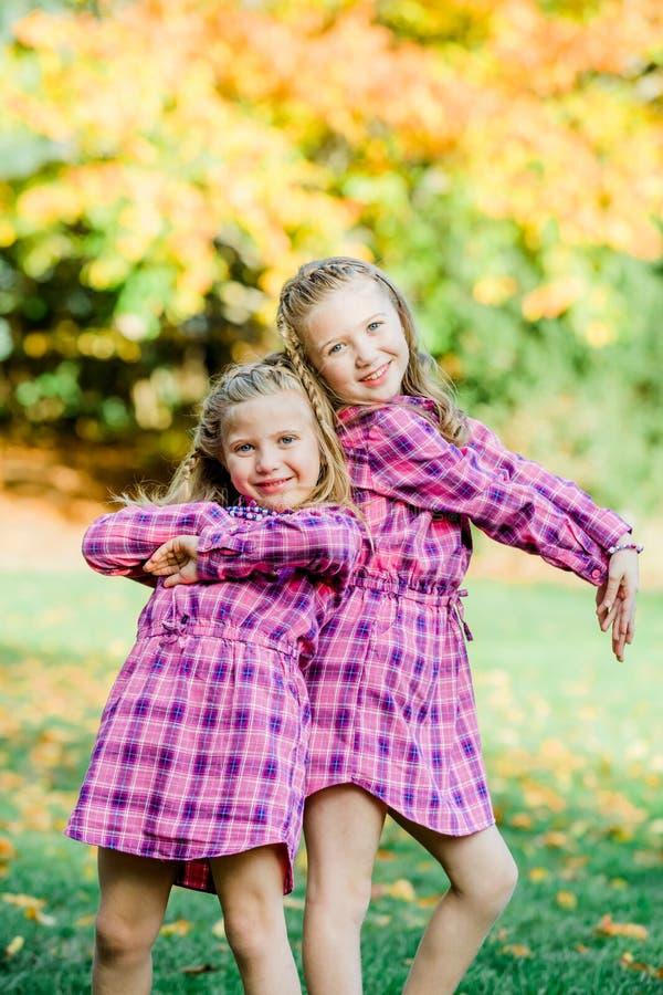 Due giovani sorelle caucasiche colpiscono una posa nell'accoppiamento dei vestiti rosa dalla flanella fotografie stock libere da diritti