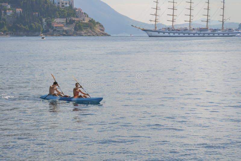 Due giovani stanno galleggiando in kajak in tandem del mare Mare che Kayaking immagini stock