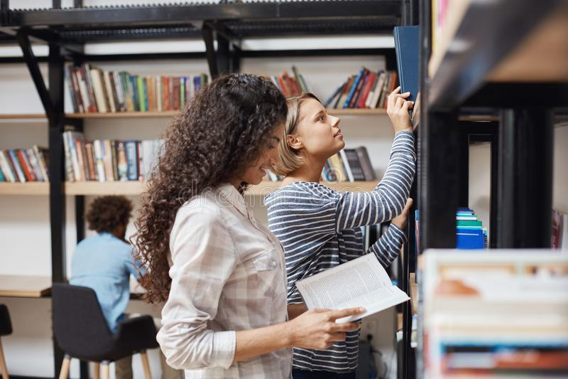 Due giovani studentesse allegre in abbigliamento casual che sta gli scaffali per libri vicini in biblioteca universitaria che gua fotografie stock libere da diritti