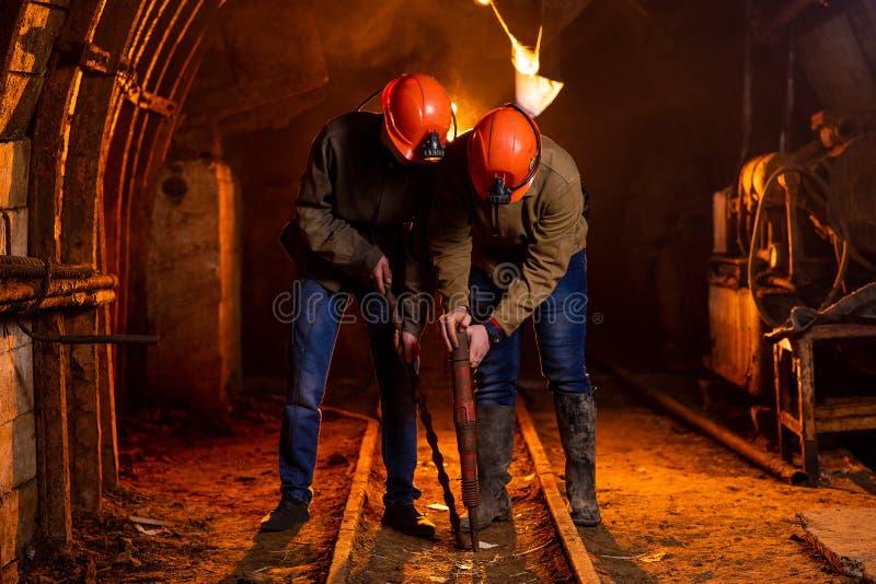 Due giovani tipi in un'uniforme funzionante e nei caschi protettivi, effettuano il lavoro nella miniera immagini stock