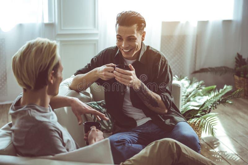 Due giovani uomini bei che bevono caffè e chiacchierata immagine stock libera da diritti