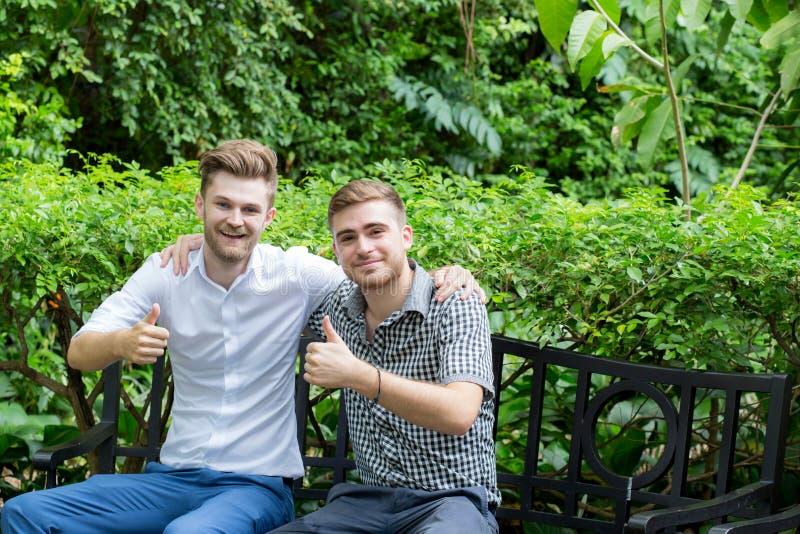 Due giovani uomini casuali felici che fanno l'approvazione sfoglia sul gesto di mano in giardino fotografia stock libera da diritti