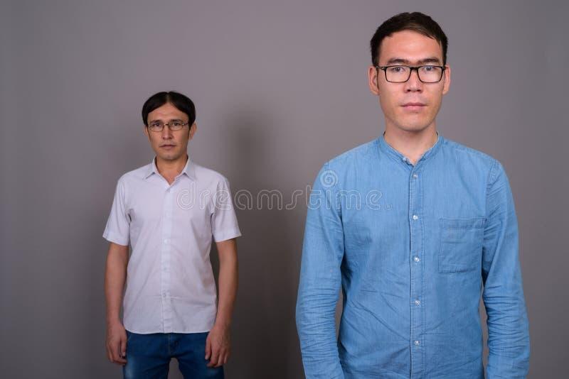 Due giovani uomini d'affari asiatici che indossano insieme gli occhiali contro immagine stock libera da diritti
