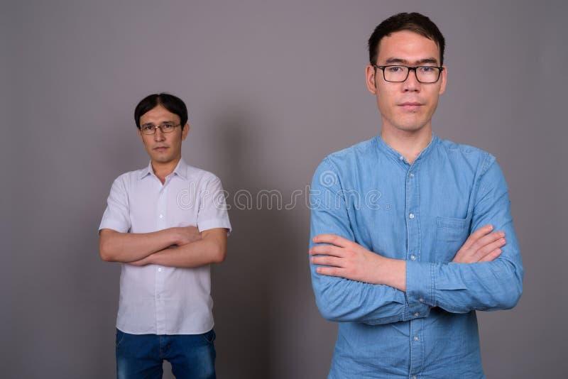 Due giovani uomini d'affari asiatici che indossano insieme gli occhiali contro fotografia stock libera da diritti