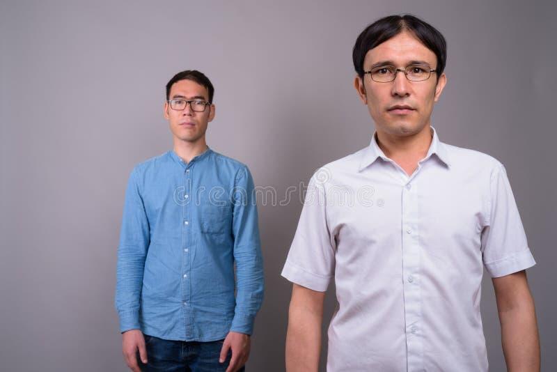 Due giovani uomini d'affari asiatici che indossano insieme gli occhiali contro immagini stock