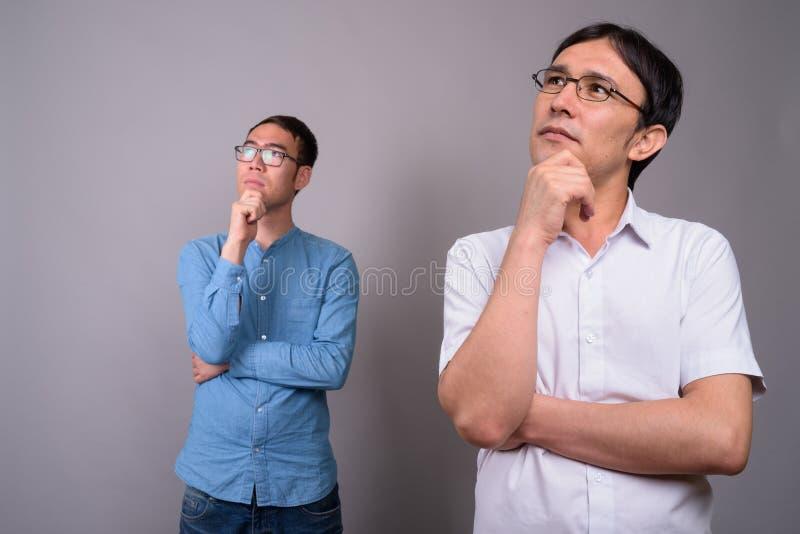 Due giovani uomini d'affari asiatici che indossano insieme gli occhiali contro fotografie stock