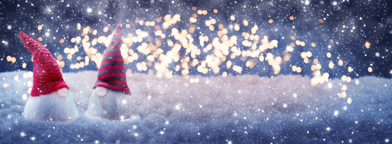 Due gnomi di Natale nella neve davanti alle luci immagine stock