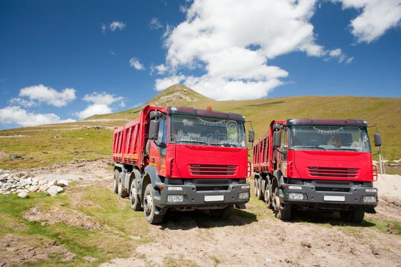 Due grandi autocarri con cassone ribaltabile rossi fotografie stock libere da diritti