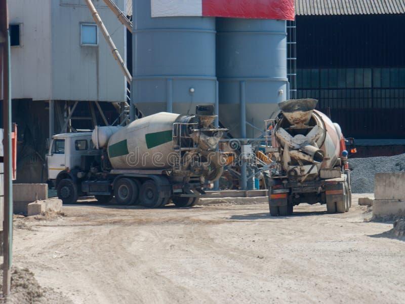 Due grandi camion del camion del cemento hanno portato il cemento alla zona industriale della pianta i fotografia stock