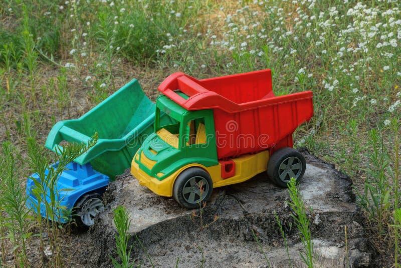 Due grandi giocattoli colorati gli autocarri con cassone ribaltabile che stanno su un ceppo fotografia stock libera da diritti