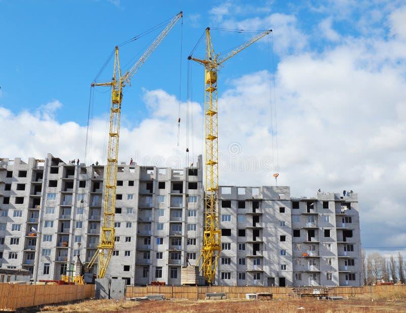 Due gru di costruzione ed aumento alto di costruzione con lo spazio della copia immagine stock
