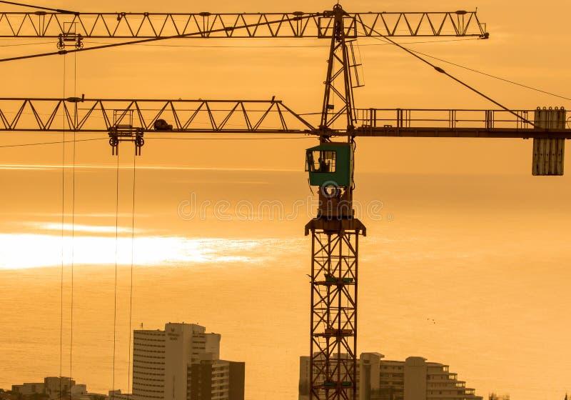 Due gru a torre della costruzione che dominano città costiera con il cielo arancio intenso all'alba fotografie stock libere da diritti