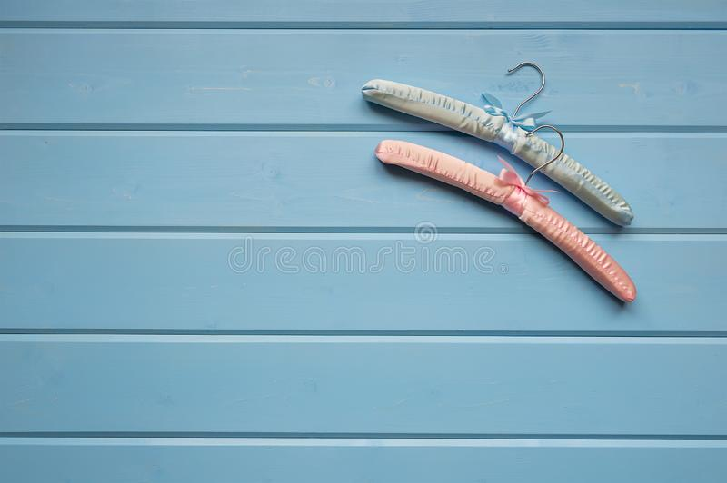 Due grucce per vestiti si trovano su un fondo di legno blu Il concetto di minimalismo Vista da sopra, un posto per testo fotografie stock libere da diritti