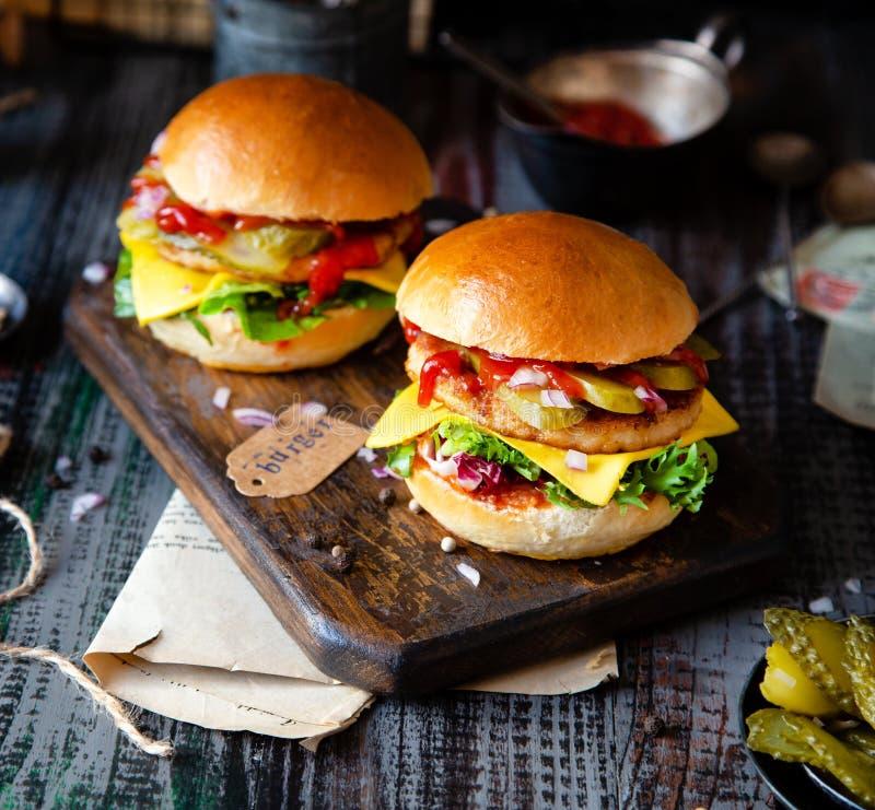Due hamburger casalinghi con pollo fritto, lattuga, formaggio, cipolla, cetrioli marinati, ketchup immagine stock libera da diritti