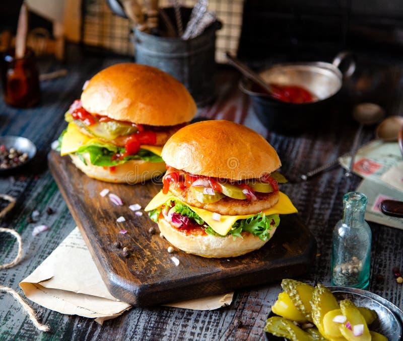 Due hamburger casalinghi con pollo fritto, lattuga, formaggio, cipolla, cetrioli marinati, ketchup immagini stock