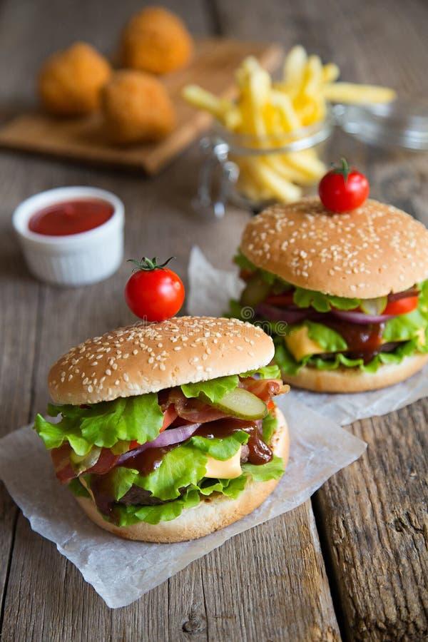 Due hamburger con le patate fritte e le palle fritte fotografia stock libera da diritti