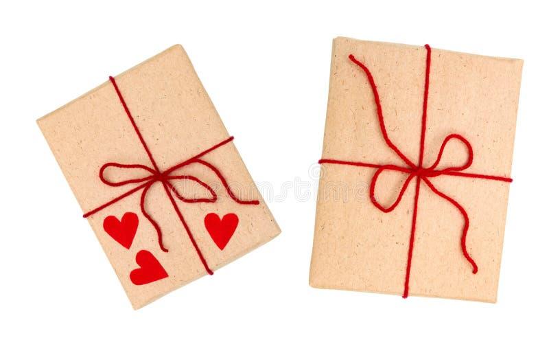 Due hanno avvolto il contenitore di regalo marrone con il nastro rosso ed il cuore da carta isolata su fondo bianco fotografia stock