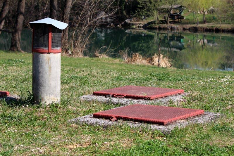 Due hanno chiuso le coperture a chiave di botola di metalli pesanti montate sul fondamento concreto circondato con il tubo concre fotografia stock libera da diritti