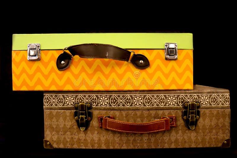 Due hanno impilato le scatole brillantemente colorate fatte come le valigie con le maniglie ed i catenacci isolati su un fondo ne fotografia stock