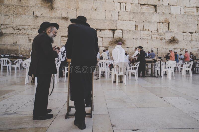 Due hanno invecchiato gli uomini ebrei religiosi stanno sul quadrato vicino alla parete ed alla conversazione occidentali Gerusal fotografia stock