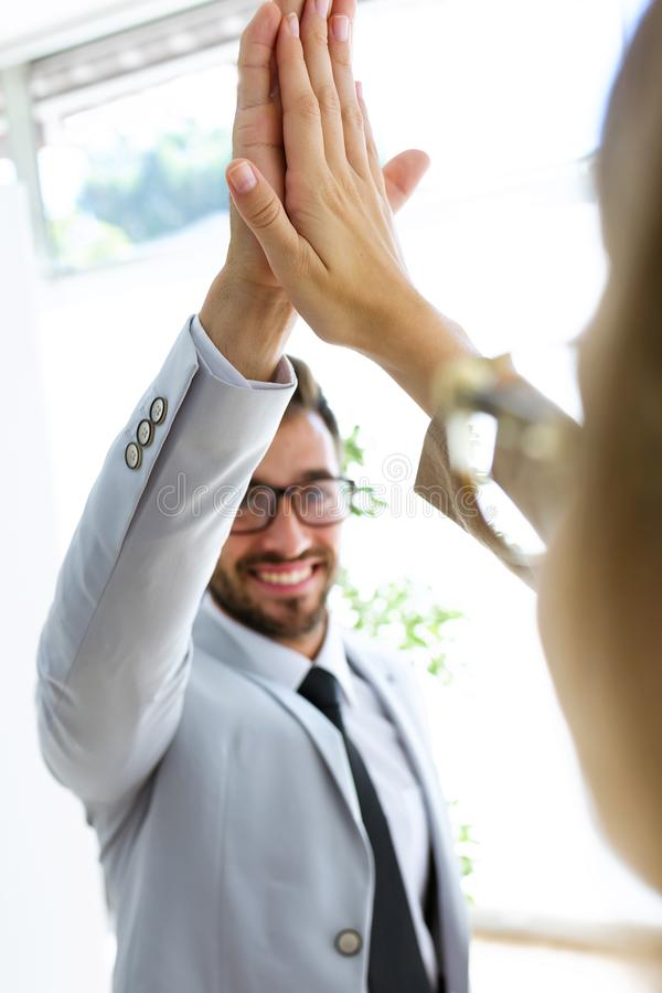 Due hanno soddisfatto i lavoratori allegri felici divertendosi sostenendo le loro mani destre in un corridoio delle loro società fotografia stock