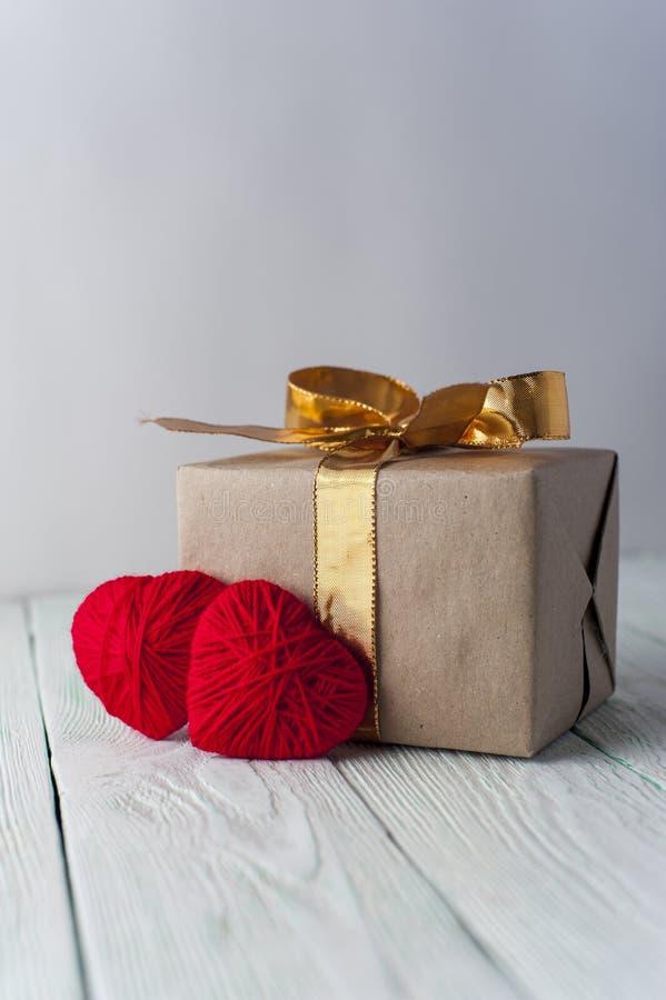 Due hanno tricottato i cuori, contenitore di regalo su fondo rustico fotografie stock