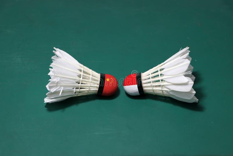 Due hanno usato i volani sul pavimento verde del campo da badminton con sia per dirigersi Una testa dipinta con la bandiera cines immagini stock