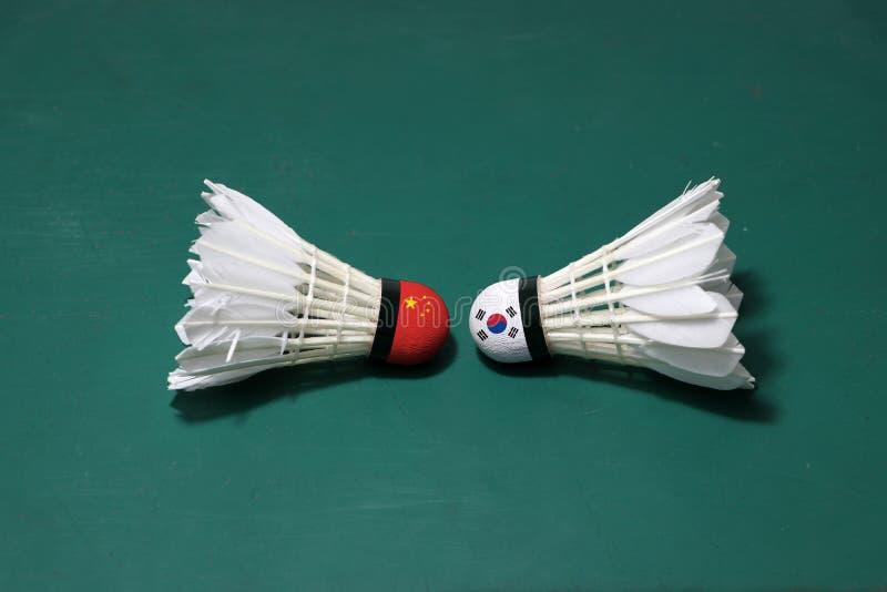 Due hanno usato i volani sul pavimento verde del campo da badminton con sia per dirigersi Una testa dipinta con la bandiera cines immagine stock