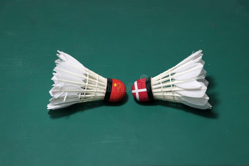 Due hanno usato i volani sul pavimento verde del campo da badminton con sia per dirigersi Una testa dipinta con la bandiera della immagini stock