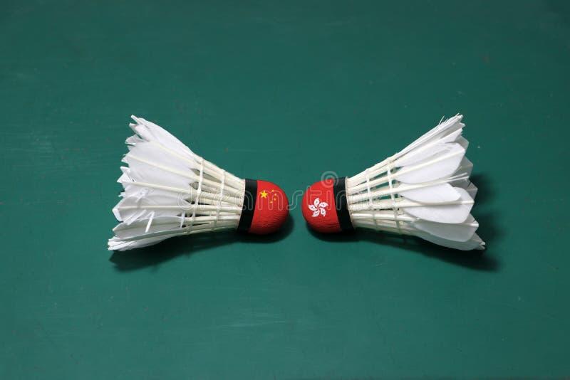 Due hanno usato i volani sul pavimento verde del campo da badminton con sia per dirigersi Una testa dipinta con la bandiera della immagine stock