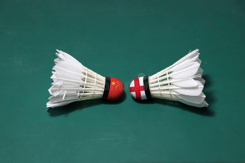 Due hanno usato i volani sul pavimento verde del campo da badminton con sia per dirigersi Una testa dipinta con la bandiera della fotografia stock
