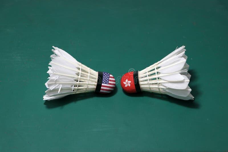 Due hanno usato i volani sul pavimento verde del campo da badminton con sia per dirigersi Una testa dipinta con la bandiera di U. fotografia stock libera da diritti