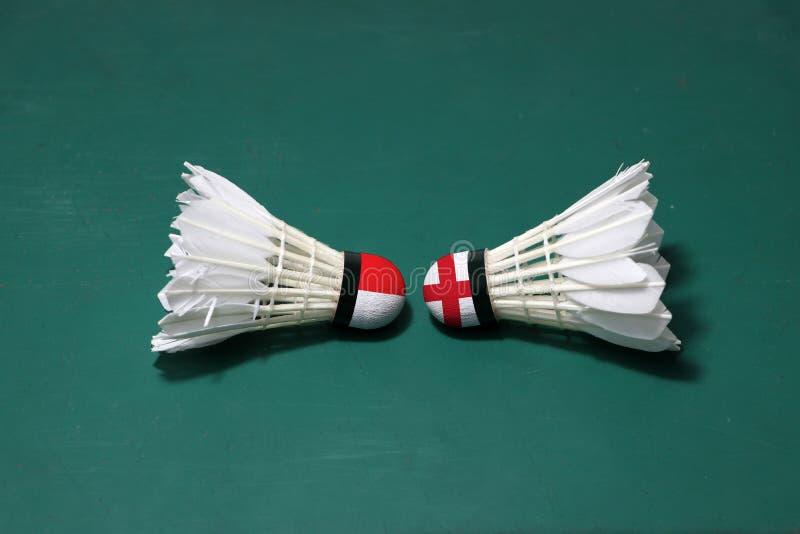 Due hanno usato i volani sul pavimento verde del campo da badminton con sia per dirigersi Una testa dipinta con la bandiera ed un fotografia stock libera da diritti