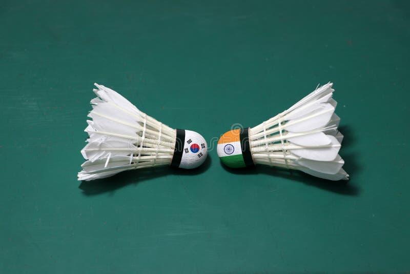 Due hanno usato i volani sul pavimento verde del campo da badminton con sia per dirigersi Una testa dipinta con la bandiera ed un immagine stock