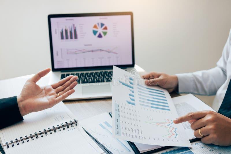 Due impiegati controllano insieme i rendiconti finanziari della società nella stanza di stima fotografie stock