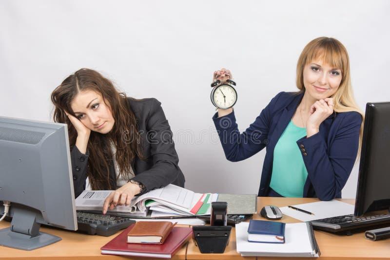 Due impiegati di concetto aspettano la conclusione del giorno lavorativo fotografia stock libera da diritti