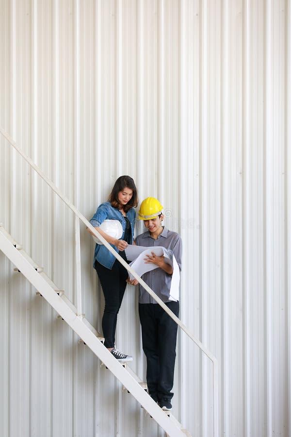 Due ingegneri asiatici, uomo e donna, discutenti nel cantiere fotografia stock