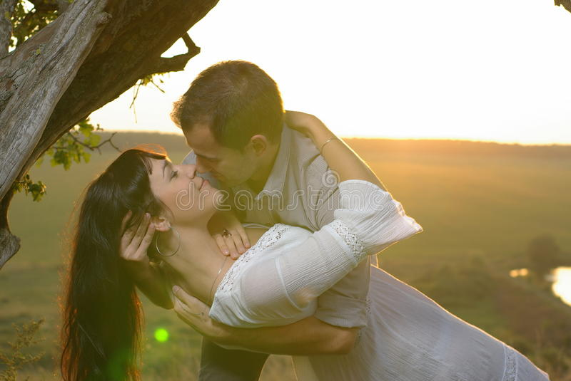Due innamorati che baciano sotto l'albero al tramonto immagini stock