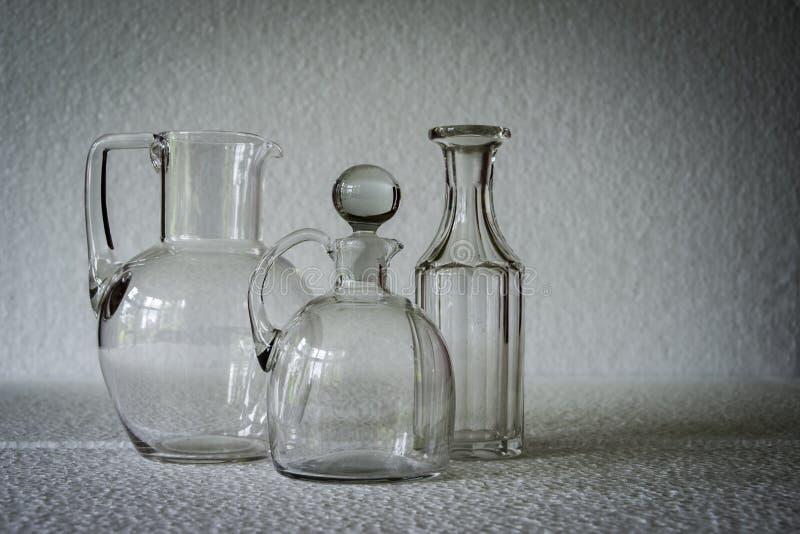 Due lanciatori del vetro trasparente e una bottiglia fotografia stock